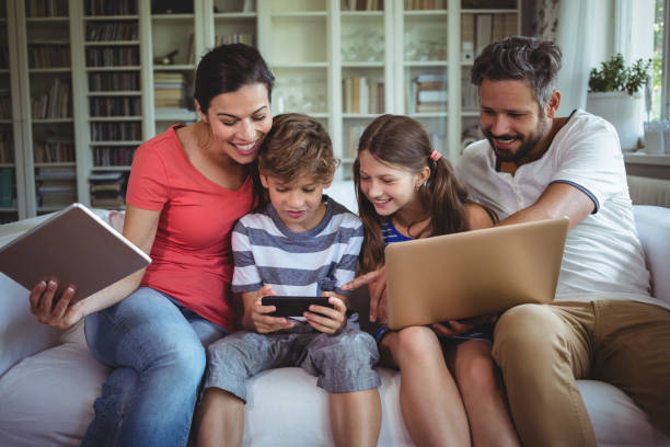 Happy family sitting on sofa and using laptop, mobile phone and digital tablet stock photo