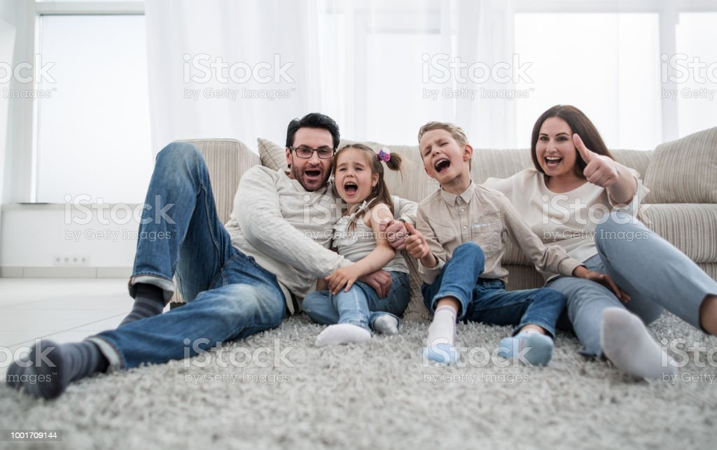 Happy Family Sitting On The Carpet In The Living Room Stock Photo -  Download Image Now