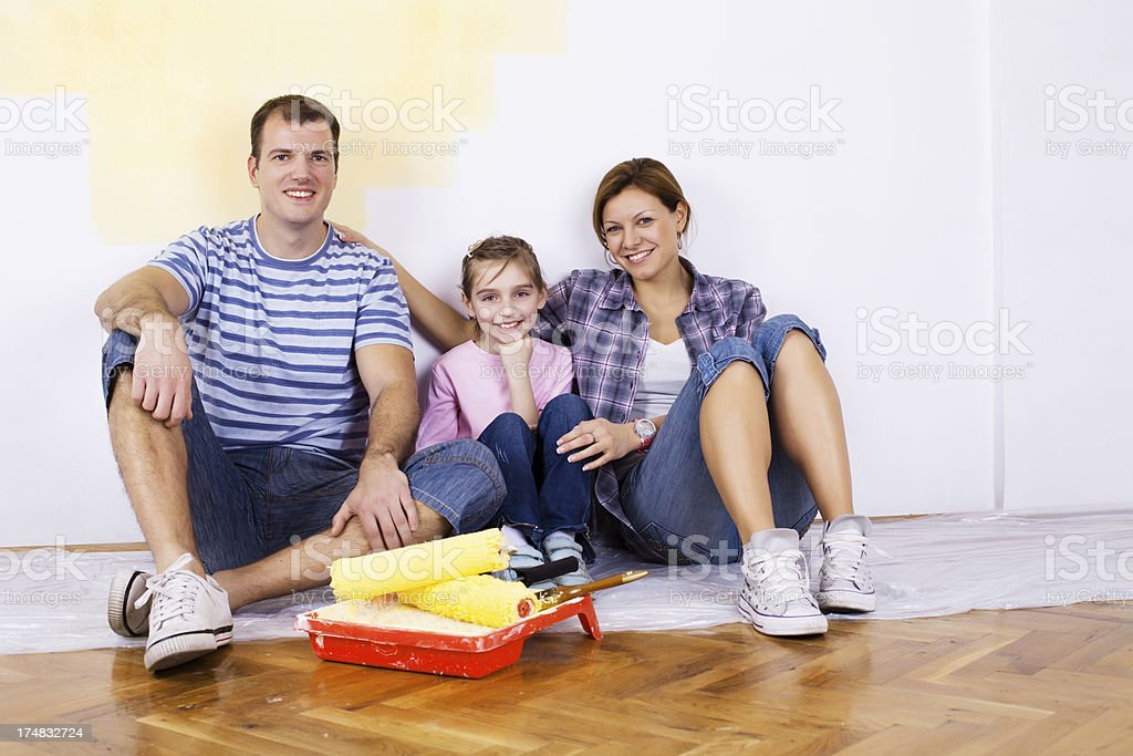 Happy family sitting on the floor after painting home royalty-free stock photo