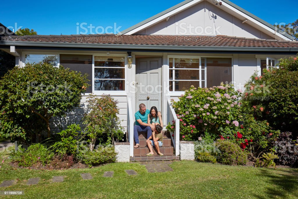 Happy family sitting outside house in summer stock photo