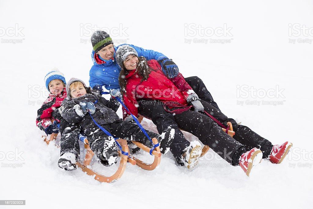 Happy family sledding on snow royalty-free stock photo