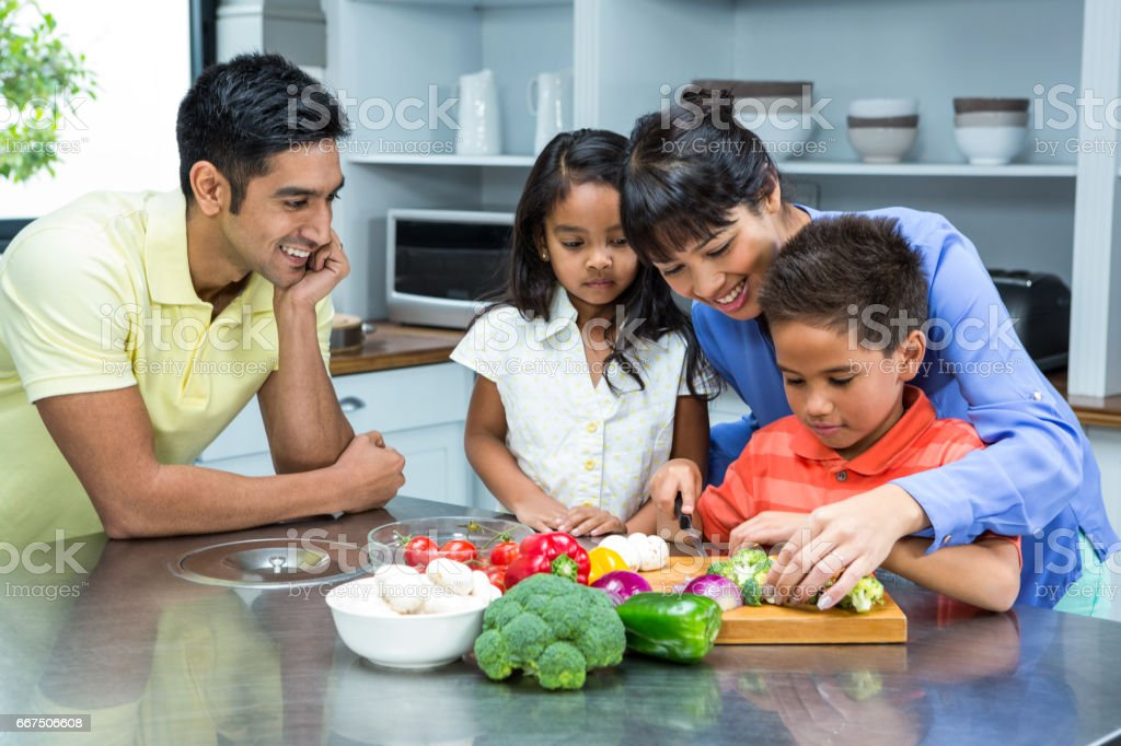Happy family slicing vegetables stock photo