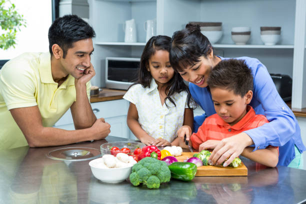 happy family slicing vegetables - kids cooking stock photos and pictures