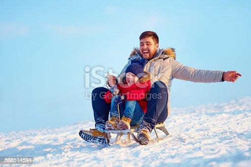 istock happy family sliding downhill on winter snow 868514594