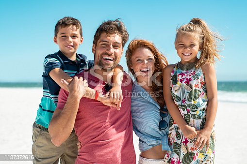 Portrait of happy family looking at camera at beach on a sunny day. Cheerful mother and father with cute daughter and son at sea during weekend. Smiling family with two children enjoying vacation at beach.