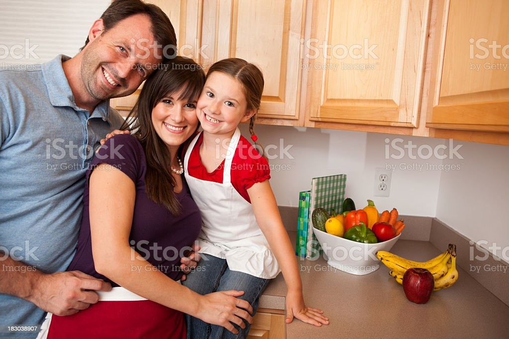 Happy Family Smiling Together in Kitchen with Fruit and Vegetables royalty-free stock photo