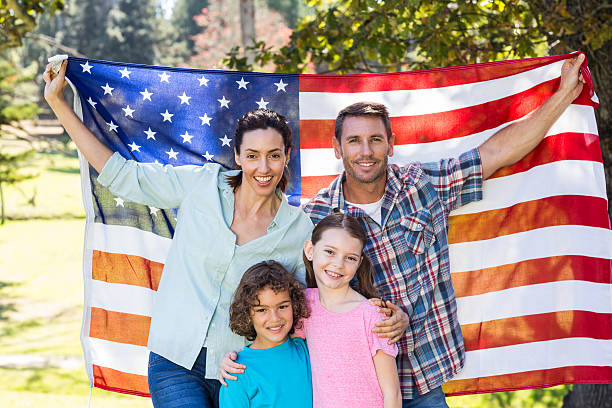 Happy family smiling with an american flag in a park stock photo