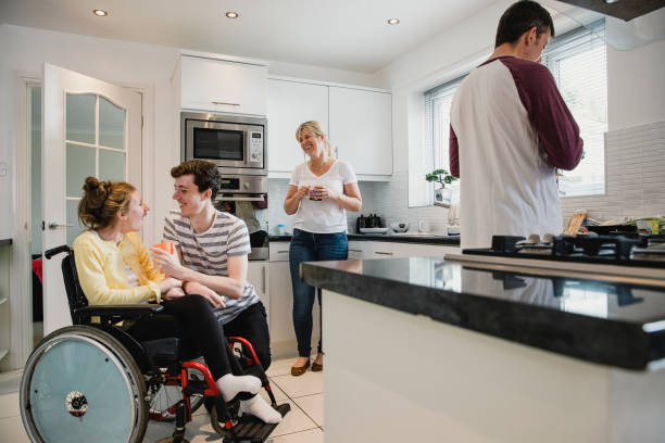 Happy Family Socialising in the Kitchen Happy family are gathered in the kitchen. The mum is watching her son interact with his disabled sister who is in a wheelchair while the father prepares lunch. amyotrophic lateral sclerosis stock pictures, royalty-free photos & images
