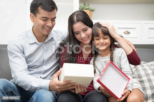 Happy Family spending time together at home.In selective focus of lovely gift box for mother's day.