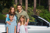 Happy family standing by their convertible smiling at camera in countryside