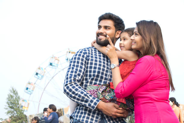 Happy family standing in front of ferris wheel Happy family standing in front of ferris wheel indian family stock pictures, royalty-free photos & images