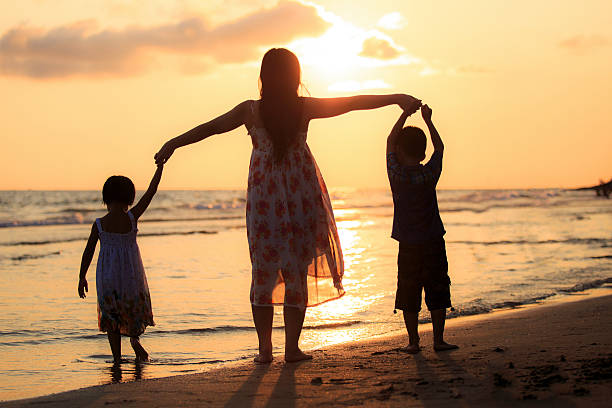 Happy family standing on the beach stock photo
