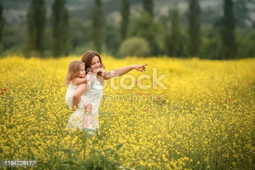480122543 istock photo Happy family summer vacation. Mother with girl in rape field enjoying life at sunset. Pretty brunette with long healthy hair. Carefree girl over yellow field and blue sky. Countryside landscape. 1194229177