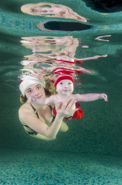 Happy family swims underwater in the pool. Mom, Dad and little boy underwater in the pool. Healthy family lifestyle and children water sports activity. Child development, disease prevention stock photo