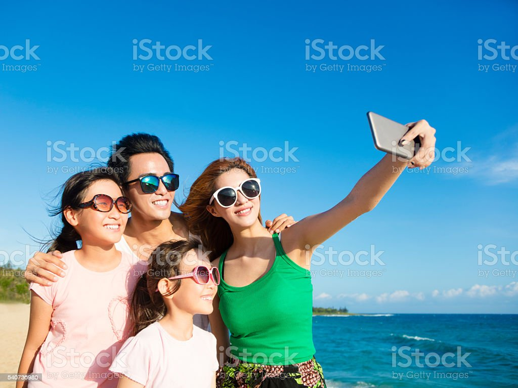 happy family taking a selfie at the beach stock photo