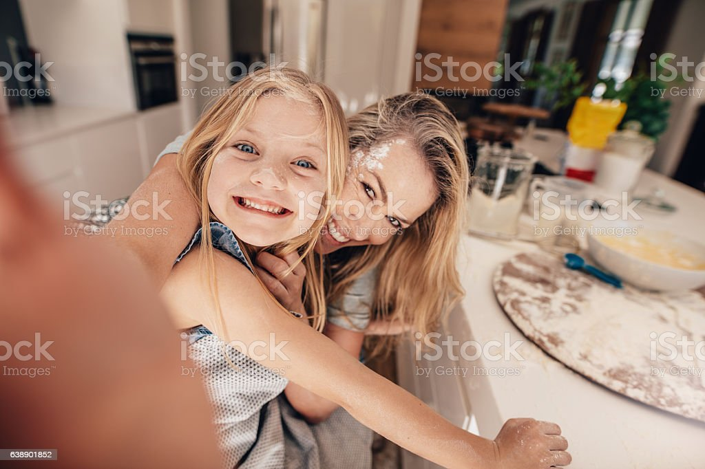 Happy family taking a selfie in kitchen stock photo