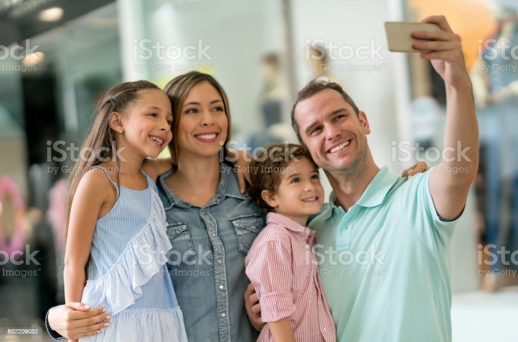 Happy family taking a selfie while shopping at the mall stock photo