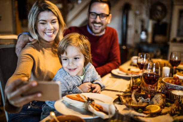 happy family taking a selfie with cell phone at dining table. - foodie stock photos and pictures