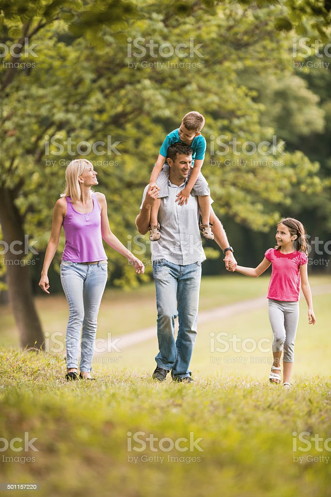 Happy parents walking with their children in nature. Father is...