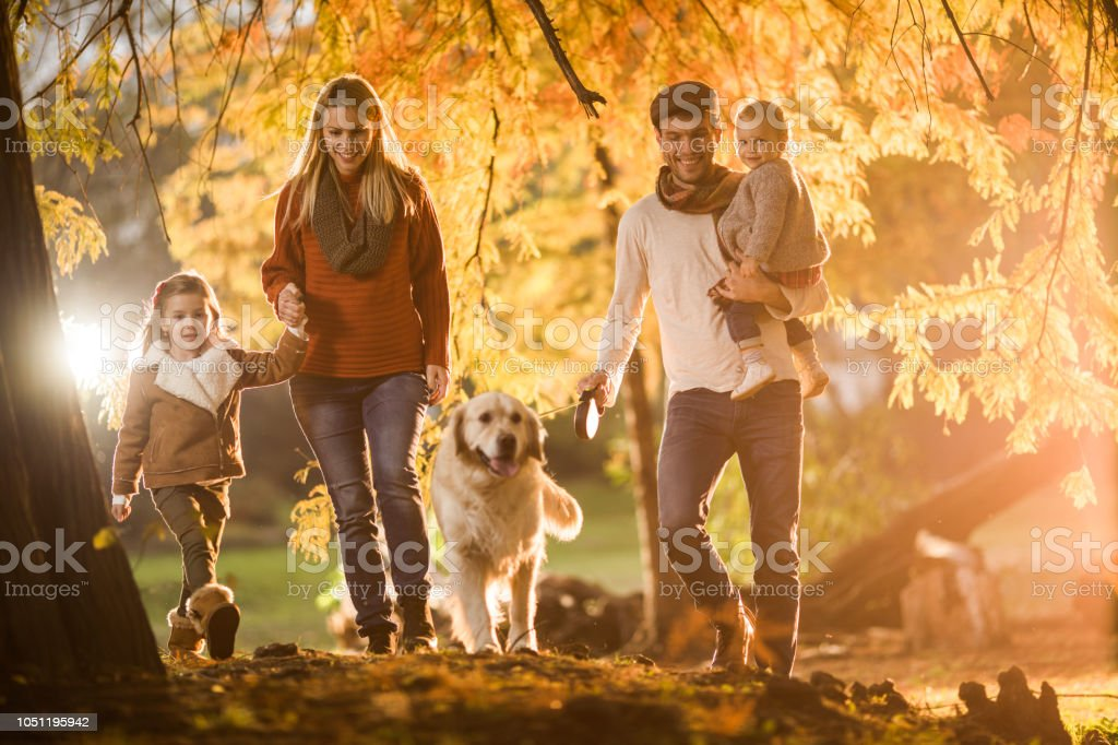 Young happy family enjoying in autumn walk with their dog at the park.