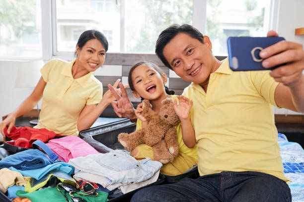 happy family taking selfie - happy mom packing some toys stock photos and pictures
