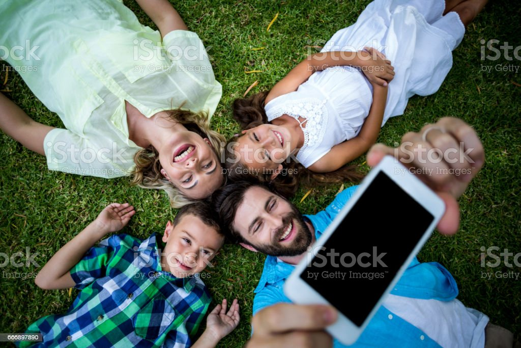 Happy family taking selfie while lying on grass in yard stock photo