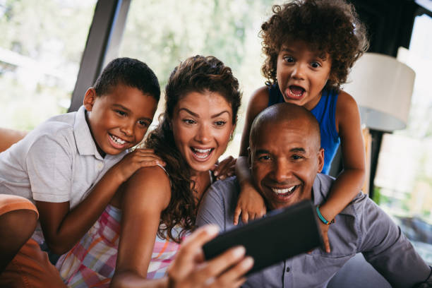 Happy family taking Selfie while sitting in cafe stock photo
