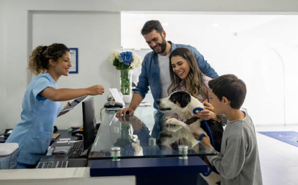 Glückliche Familie bringt ihren Hund zum Tierarzt – Foto