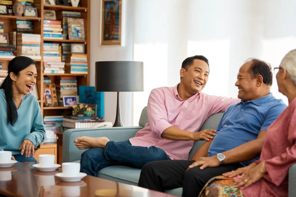Happy family talking enjoying coffee at home Happy family talking while sitting in living room. Males and females are enjoying coffee at home. They are spending leisure time together. old mother son asian stock pictures, royalty-free photos & images