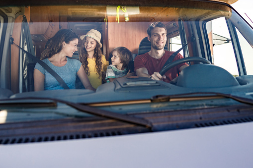 Happy family talking while driving inside of a camp trailer.