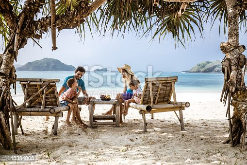 Happy parents and their small kids communicating while relaxing on deck chairs in a shade at the beach.