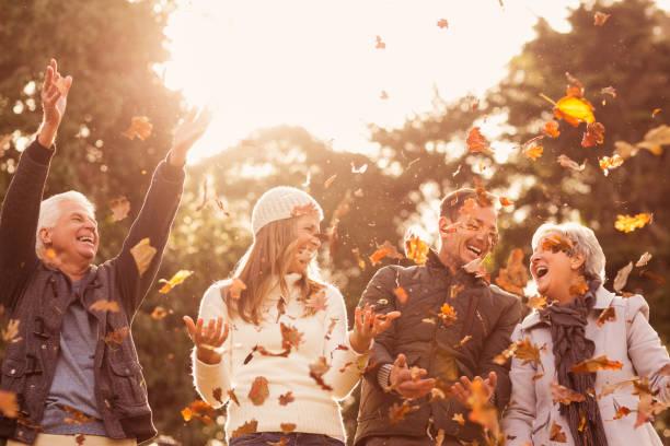 glückliche familie wirft blätter rund um - 70 jahre kleidung stock-fotos und bilder