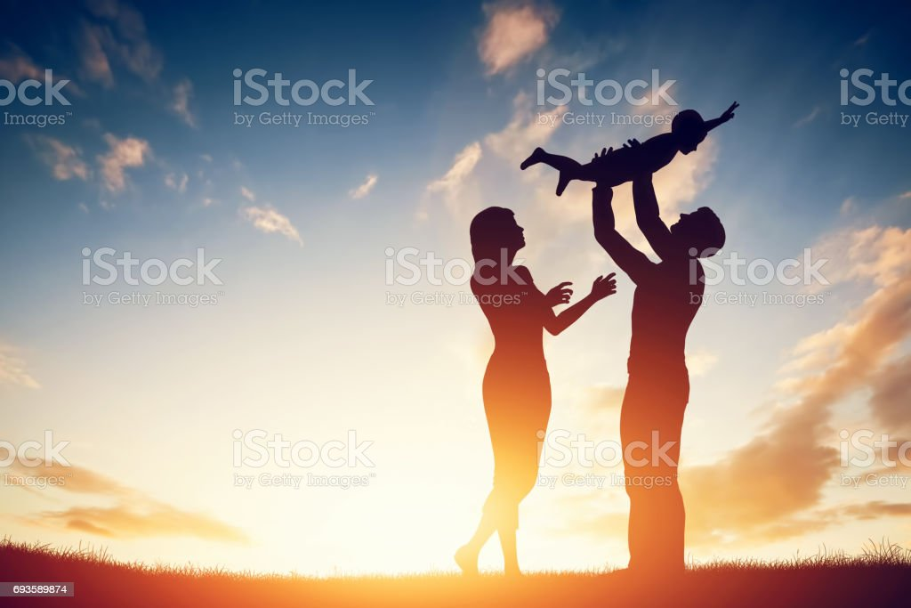 Happy family together, parents with their little child at sunset. stock photo