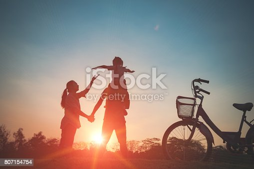 istock Happy family together, parents with their little child at sunset. 807154754