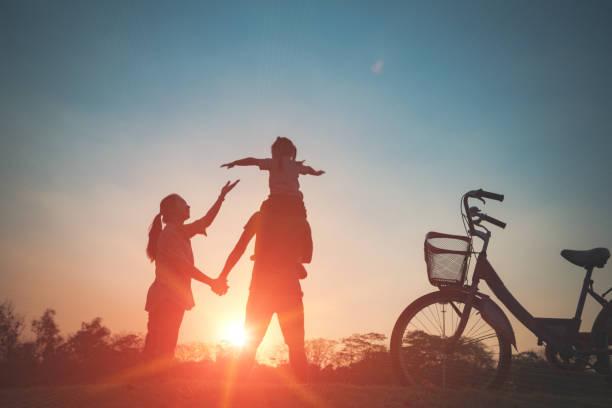 küçük çocuklarının gün batımında ile mutlu aile birlikte, anne. - arkadan aydınlatmalı stok fotoğraflar ve resimler