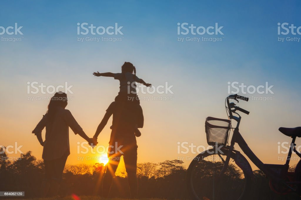 Happy family together, parents with their little child at sunset. Father raising baby up in the airing. stock photo