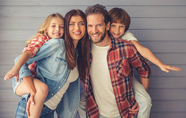 Happy family together Beautiful young parents and their children are looking at camera and smiling, on gray wall background four people stock pictures, royalty-free photos & images