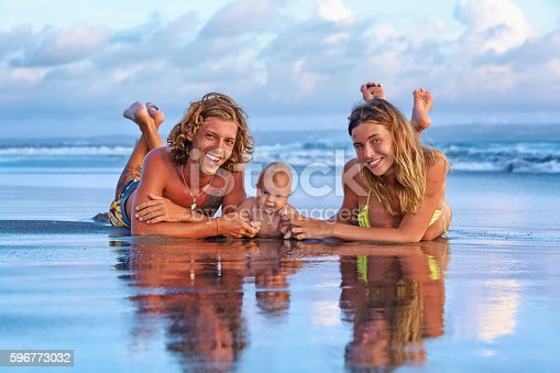 istock Happy family travel. Father, mother, baby son on sunset beach 596773032