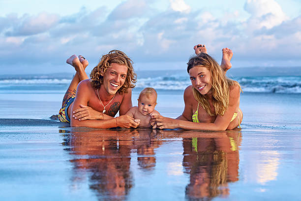 happy family travel. father, mother, baby son on sunset beach - pool schritte stock-fotos und bilder