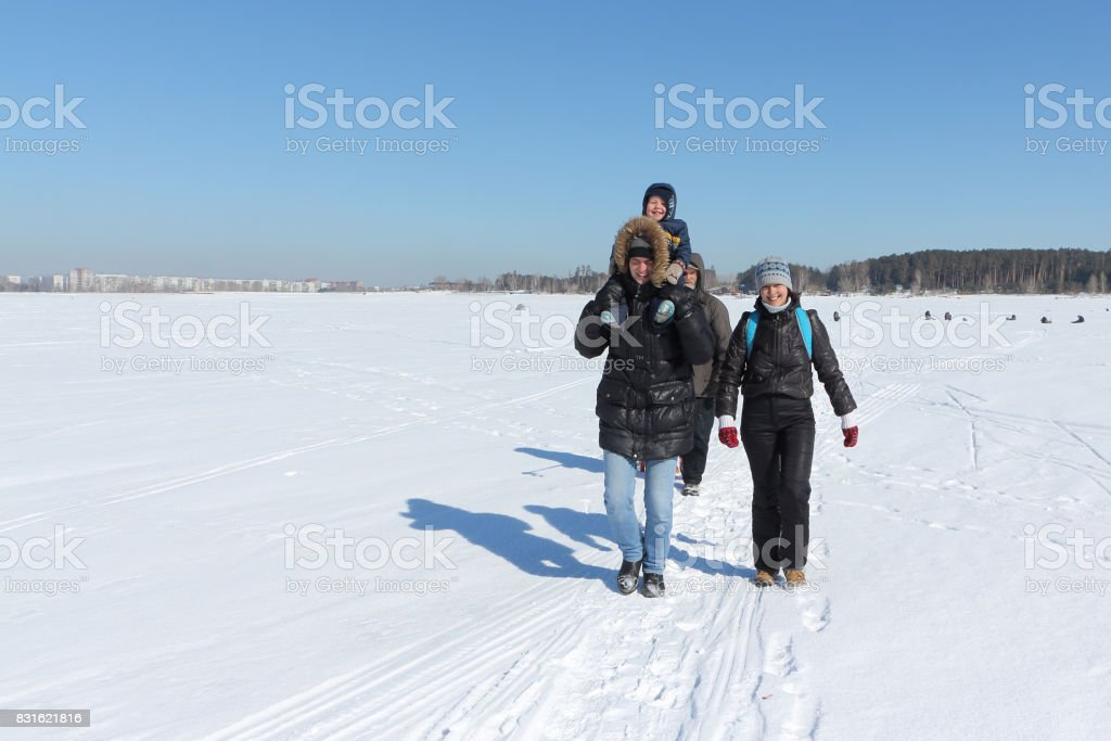 Happy family traveling around the snow river in the winter stock photo