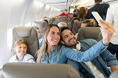 Happy family traveling by plane and taking a selfie with a cell phone while smiling - travel concepts