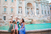 istock Happy family trowing coins at Trevi Fountain, Rome, for good luck. Little girls and parents making a wish to come back. 655529622