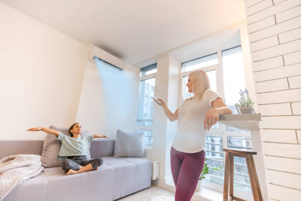 Happy family under air conditioner, mom holding remote control switch on conditioning in living room adjust comfort temperature for daughter, climate system at modern home stock photo