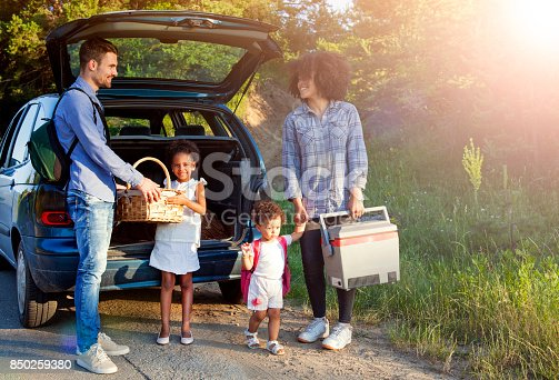 807410158 istock photo Happy family unloading luggage from the car for summer vacation. 850259380