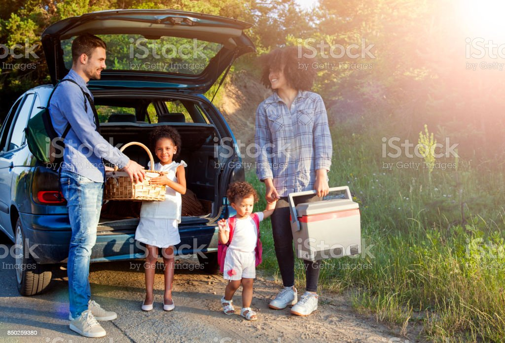 Happy family unloading luggage from the car for summer vacation. stock photo