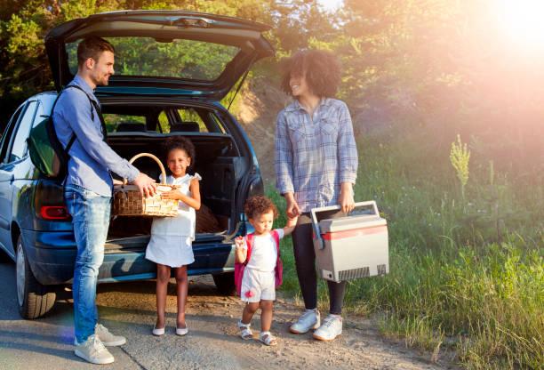 Glückliche Familie entladen Gepäck aus dem Auto für Sommerurlaub. – Foto