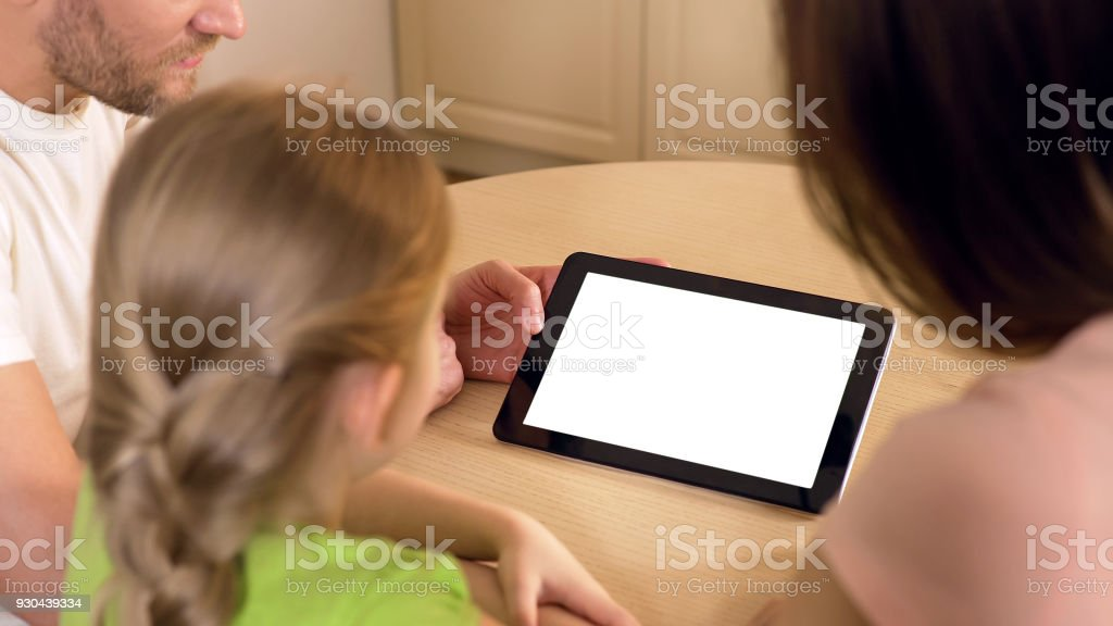 Happy family using application on tablet pc with pre-keyed green touchscreen stock photo