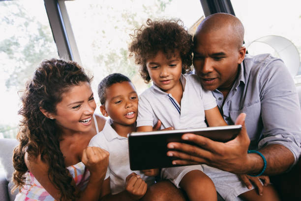 Happy family using digital tablet in cafe stock photo