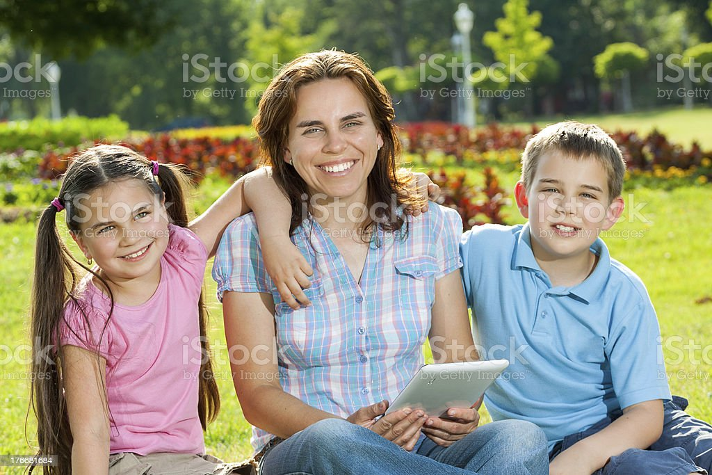 Happy Family using laptop lying on grass royalty-free stock photo