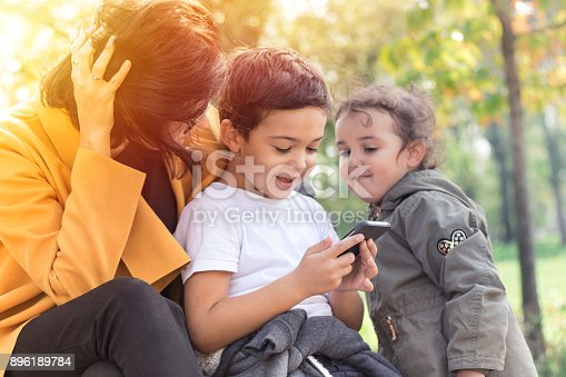 istock Happy family using mobile phone in the park. 896189784